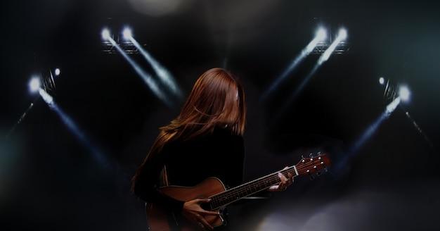 Красивая азиатская женщина с длинными каштановыми черными волосами играет на гитаре и поет песню на сцене с зажженным дымом, неизвестный человек носит черную ткань