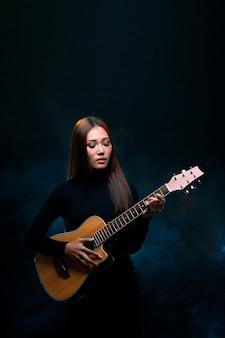 Красивая азиатская женщина с длинными каштановыми черными волосами играет на гитаре и поет песню на сцене с зажигающим дымом