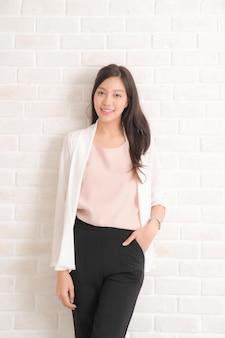 Красивая азиатская женщина с длинными каштановыми волосами улыбается и смотрит на ее вид сбоку с носить черные футболку и джинсы, стоя positng на стене бежевого цвета.