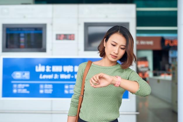아름다운 아시아 여성은 시간을 확인하기 위해 손목시계를 봅니다.