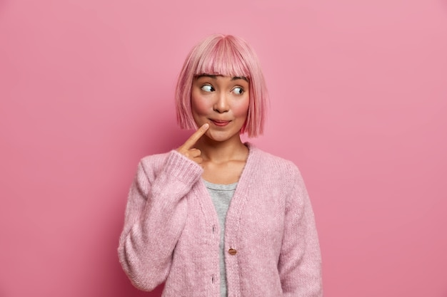 Beautiful asian woman looks with surprised curious expression on right side, keeps index finger near mouth, has dyed rosy hair, models indoor, dressed in comfortable sweater. thoughtful charming lady