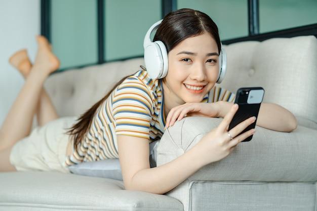 ソファに横になって、電話を使用しながら音楽を聴いている美しいアジアの女性
