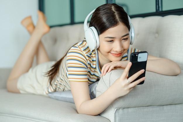 ソファに横になって、電話を使用しながら音楽を聴く美しいアジアの女性