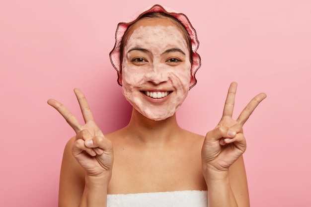 Beautiful asian woman makes peace gesture with both hands, smiles positively, washes face with bubble soap, cares about hygiene, enjoys freshness after taking bath