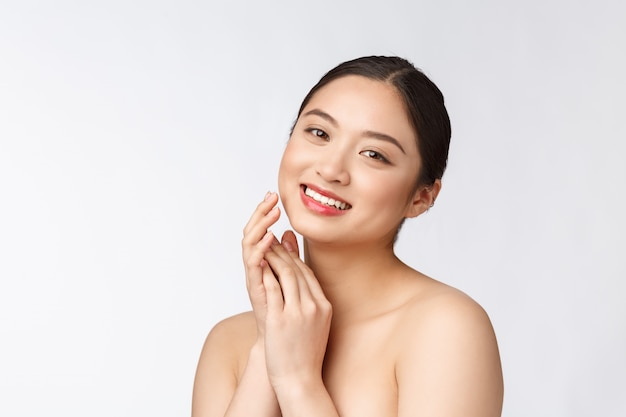 化粧品の美しいアジアの女性の化粧、女の子の手タッチ頬と笑顔、白い壁に分離されたウェルネスと完璧な美しさの顔