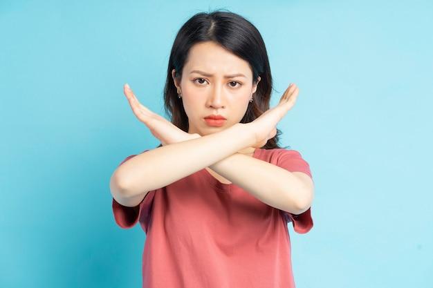 화난 얼굴로 손으로 x를 만드는 아름다운 아시아 여자
