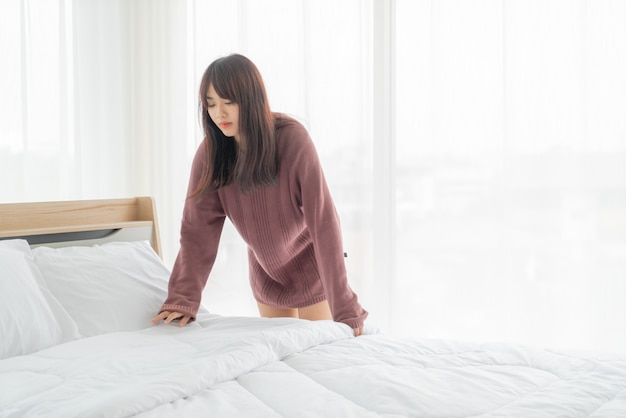 Beautiful asian woman making bed in room with white clean sheet
