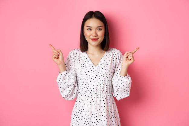 Bella donna asiatica che fa una scelta per lo shopping, puntando le dita lateralmente e mostrando varianti, sorridendo alla telecamera, in piedi su sfondo rosa