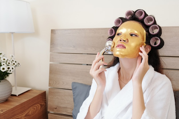 Beautiful asian woman massaging her face with golden silicone mask on after taking eveing shower