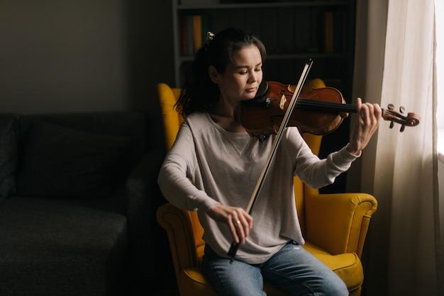 Красивый азиатский музыкант женщины играет на скрипке, сидя на мягком стуле в комнате с современным интерьером. девушка занимается игрой на музыкальном инструменте дома.