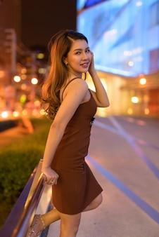 Beautiful asian woman outdoors in bangkok, thailand at night
