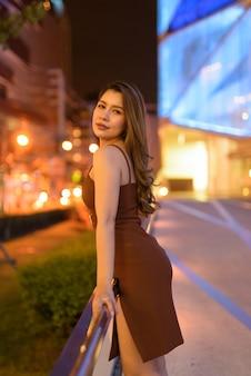 Красивая азиатская женщина на открытом воздухе в бангкоке, таиланд ночью