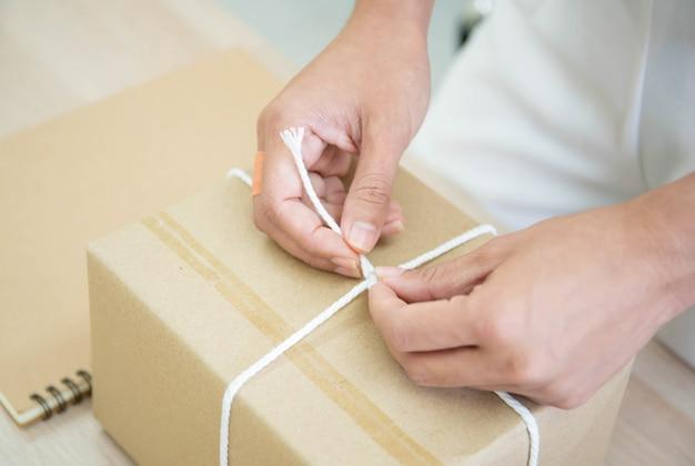 Красивая азиатская женщина пакуя почтовый пакет на таблице, онлайн-покупках и электронной коммерции в малом стартапе.