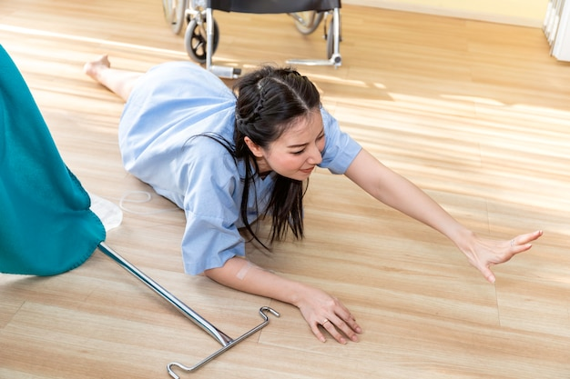 Beautiful asian woman patient accident falling down and crawling for help in hospital room.
