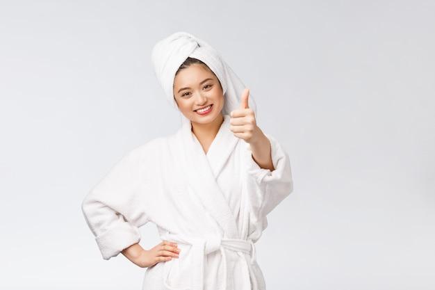 Кожа красивой азиатской женщины совершенная показывая вверх изолированные большие пальцы руки