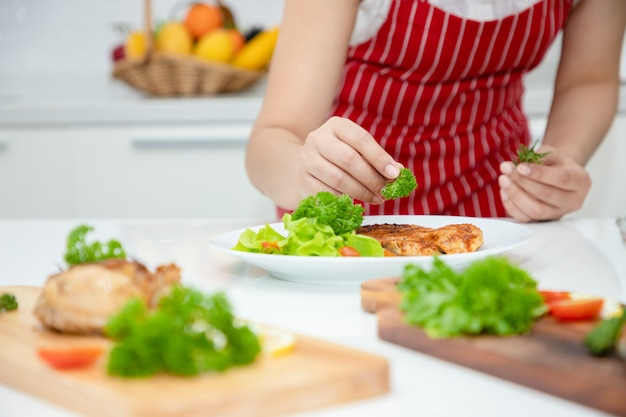 A beautiful asian woman places parsley on a salmon steak arranged on a plate with green oak vegetables ideas about healthy cooking and weight loss