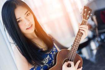 Beautiful Asian Woman Playing Ukulele with happiness