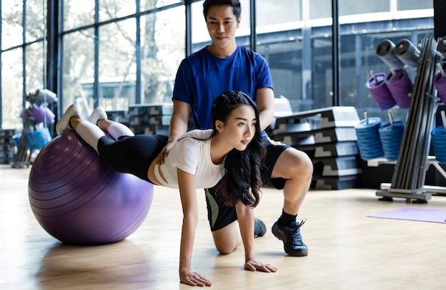 Красивая азиатская женщина играет йогу мячом йоги с мужчиной тренера в тренажерном зале в концепции тренировки в тренажерном зале. молодые пары с тренировки, вместе занимаясь йогой в помещении.