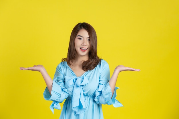 Beautiful asian woman pointing hand to empty space aside on yellow wall