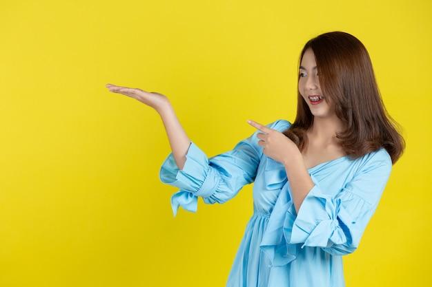 黄色の壁の脇の空きスペースに手を指している美しいアジアの女性