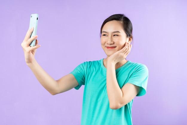 美しいアジアの女性の肖像画、紫色の背景で隔離