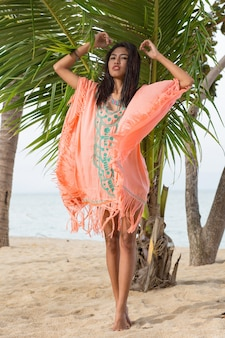 熱帯の植物や葉でポーズをとる美しいアジアの女性。刺繡とタッセルが付いた流行の自由奔放に生きるビーチドレスを着ています。ジュエリー、ブレスレット、ネックレス。