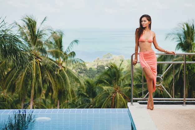 Beautiful asian woman posing in pink bikini swimsuit and pareo on terrace on tropical villa smiling happy on vacation in thailnad, sexy body summer style