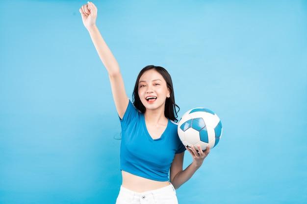 青のサッカーボールでポーズをとって美しいアジアの女性