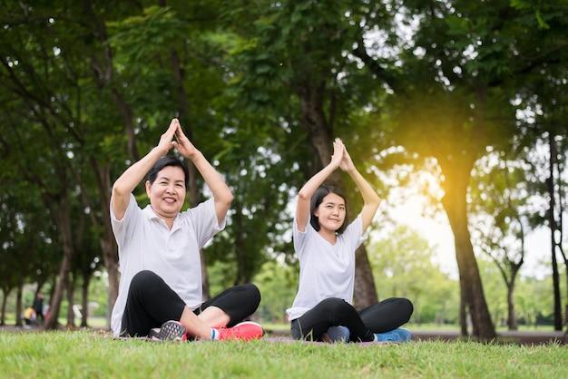 아침에 공공 공원에서 요가를 하는 아름다운 아시아 여성, 행복하고 웃고, 긍정적인 생각, 건강 및 생활 방식 개념