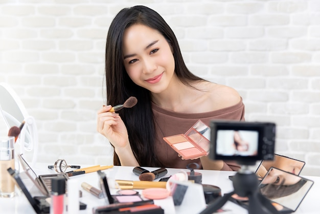 Beautiful asian woman professional beauty vlogger recording makeup tutorial video