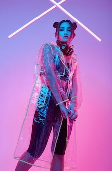 Beautiful asian woman in a raincoat listens music in headphones around colorful neon