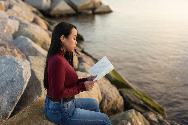 Beautiful asian woman reading a book in front of the sea