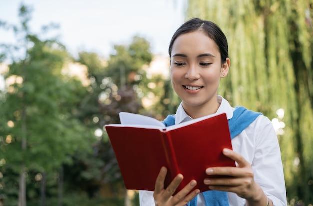 本を読んで美しいアジアの女性。笑顔の学生の勉強、言語の学習、公園に座って、教育の概念