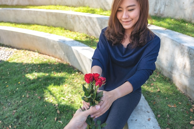 A beautiful asian woman receiving red rose flowers from boyfriend on valentine's day in the outdoors