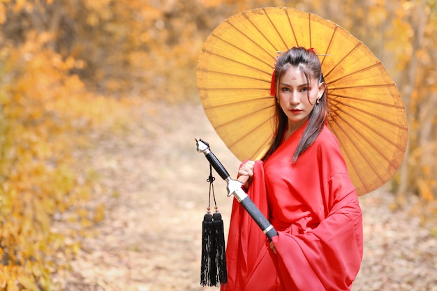 Beautiful asian woman in red chinese costume with ancient umbrella and black ancient sword with peaceful