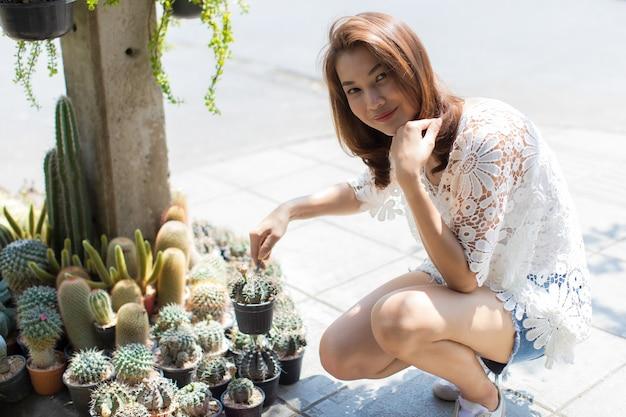 Красивая азиатская женщина, выбирая кактус в цветочном магазине, образ жизни современной домохозяйки.