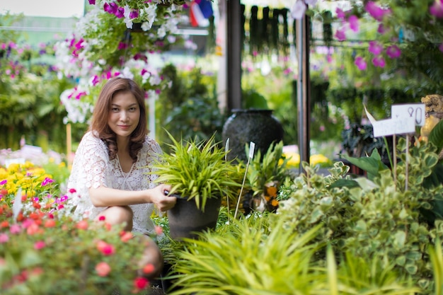 Beautiful asian woman selecting flower in floral shop, lifestyle of modern housewife.