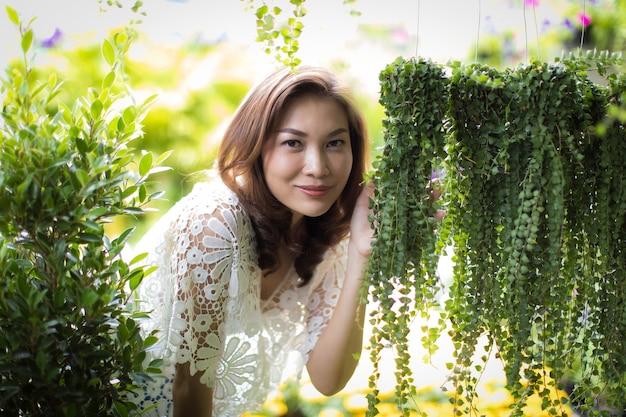 Красивая азиатская женщина, выбирая цветок в цветочном магазине, образ жизни современной домохозяйки.