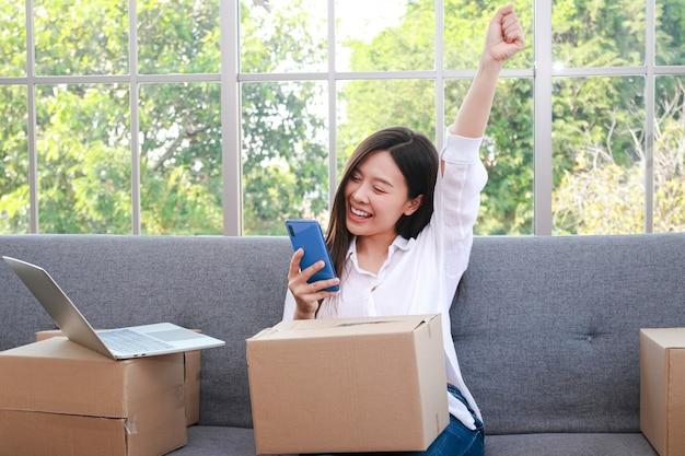 아름다운 아시아 여성이 온라인으로 판매합니다. 스마트폰으로 주문을 받게 되어 기쁩니다. 기업가 개념 온라인으로 사업을 하고 우편으로 상품을 보냅니다.