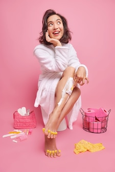 Beautiful asian woman shaves legs in wash room makes pedicure prepares for date wants to have fabulous look wears white bathrobe poses on toilet seat thinks about coming party smiles gladfully