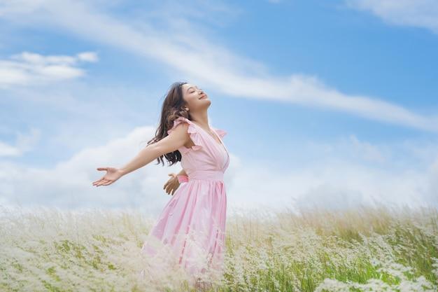 美しいアジアの女性彼女は牧草地で自由を持っています。彼女は幸せだ。