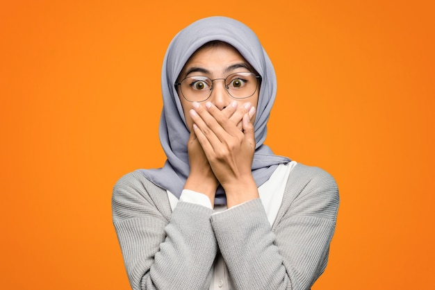 Beautiful asian woman shocked covering mouth with hand