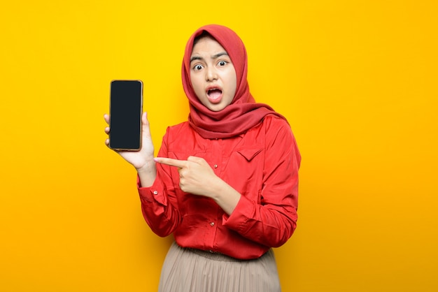 Beautiful asian woman shocked and pointing to smartphone