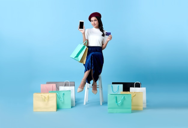 Beautiful asian woman shopper sitting and carrying shopping bags with showing mobile phone and credit card in hands on blue.