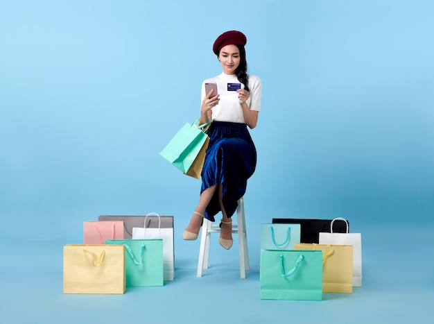 Beautiful asian woman shopper sitting and carrying shopping bags with using credit card and mobile phone in hands on blue space.