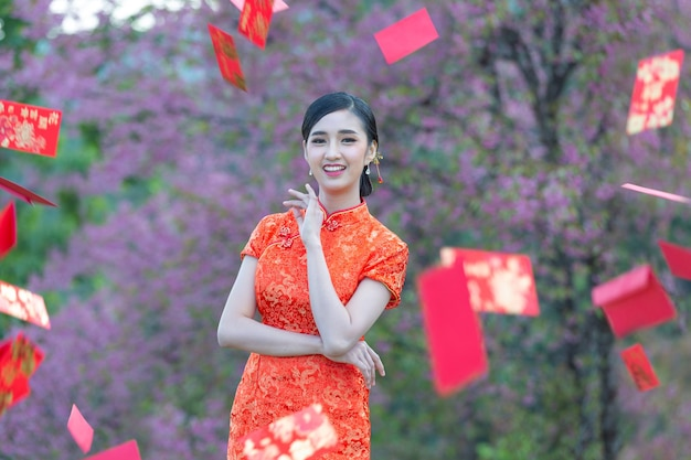 美しいアジアの女性が何かを見せ、中国の旧正月に赤い封筒を取る