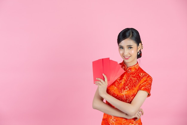Красивая азиатская женщина что-то показывает и берет красные конверты в китайском новом году