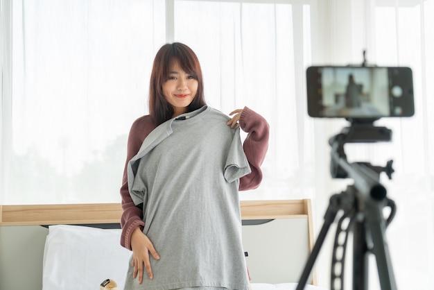 Vlog를 녹화하기 위해 카메라에 옷을 보여주는 아름 다운 아시아 여자