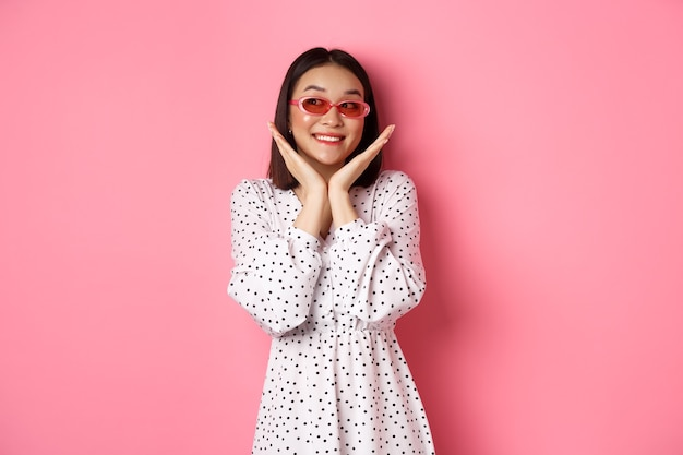 Beautiful asian woman showing her clean cute face, wearing sunglasses, smiling and looking aside with admiration, standing over pink.
