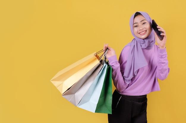 Красивая азиатская женщина показывает хозяйственные сумки, нося фиолетовую футболку, используя мобильный телефон